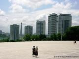 Blick ueber den Platz auf Wohnhaeuser und den Juche Turm