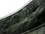 Ein Bronzerelief umgibt das Parteiemblem