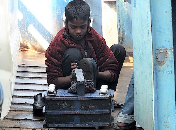 Ein Junge verdient sich Geld als Schuhputzer auf der Fähre