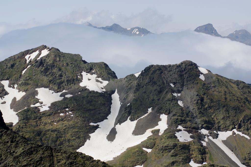 Blick-vom-Gipfel-ueber Schneefelder-und-Berge
