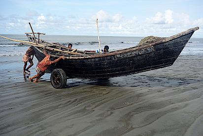 Fischer-ziehen-ihr-Boot-an-Land