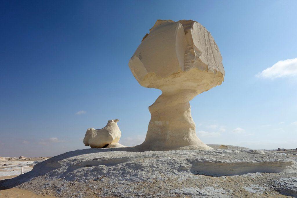 Kalksteinfelsen-in-Pilzform-mit-daneben-sitzendem-Huhn