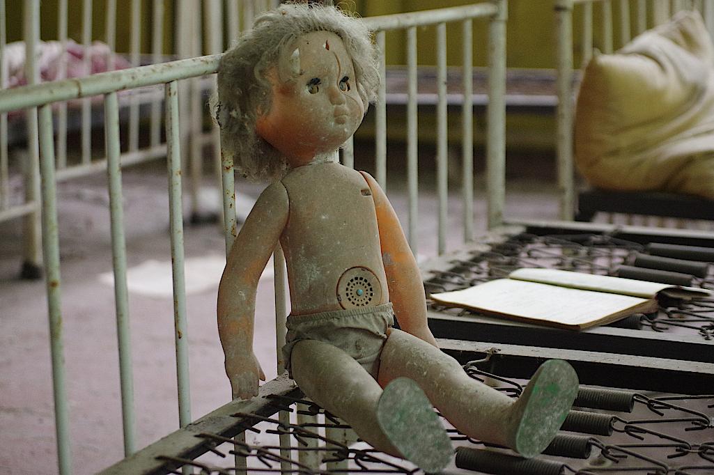 Eine-Puppe-sitzt-auf-einem-Bettgestell
