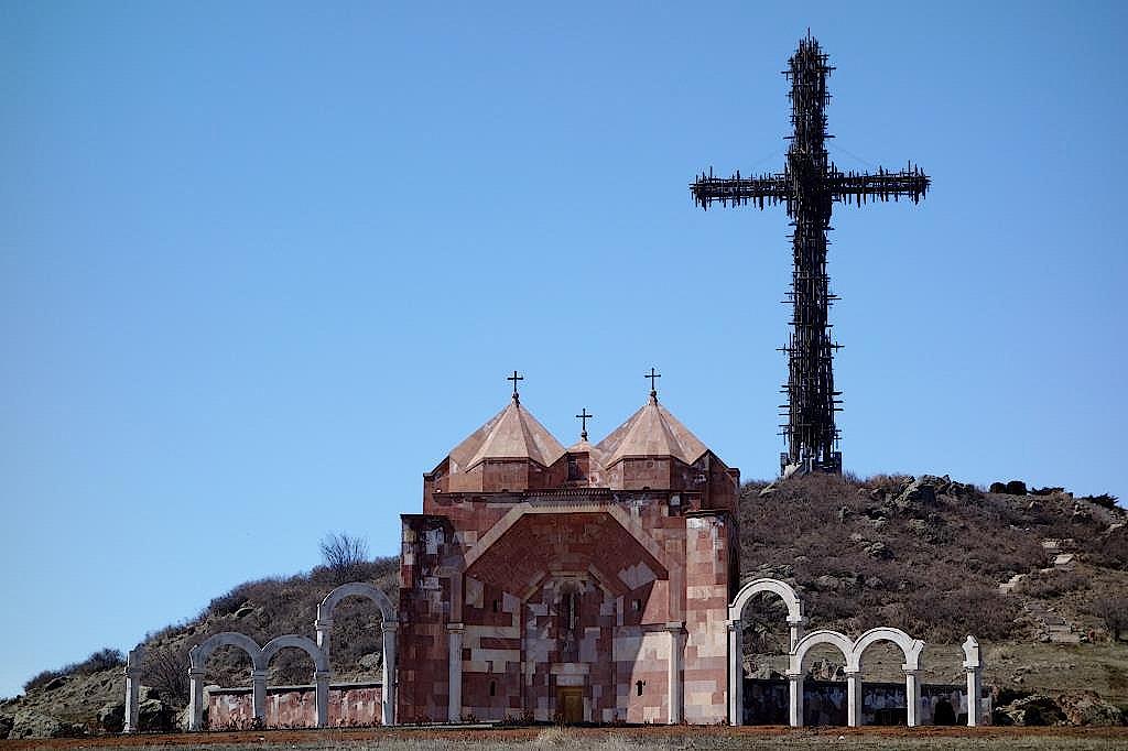 Kapelle vor einem Kreuz aus Rohren