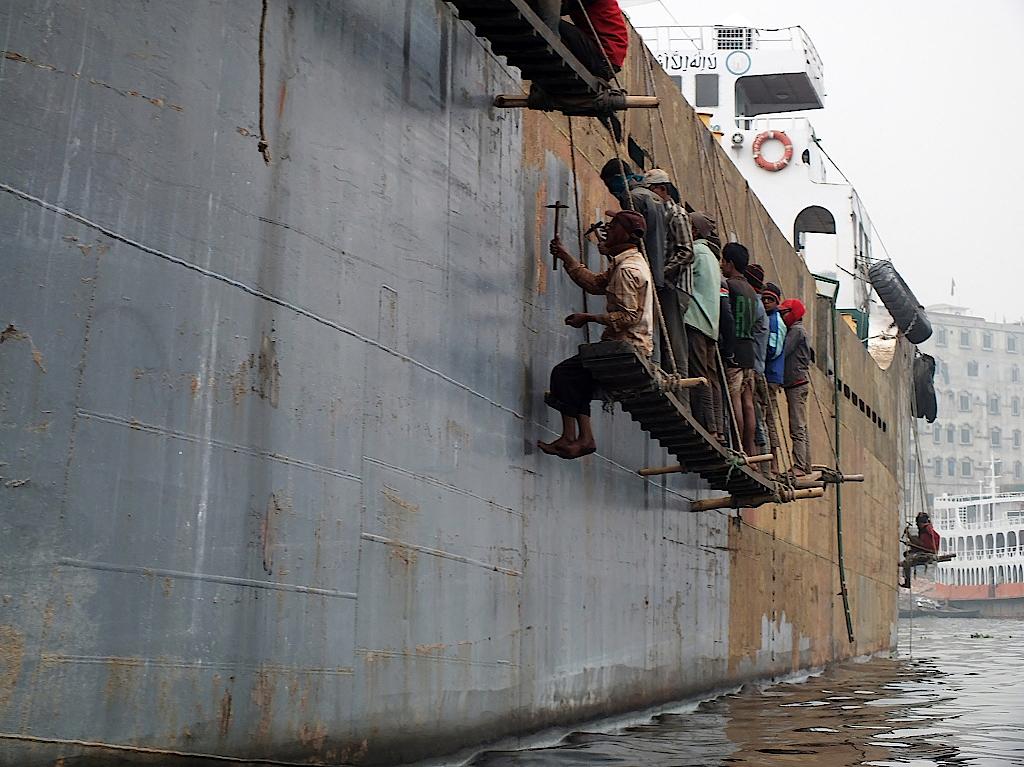 Arbeiter bearbeiten einen Schiffsrumpf