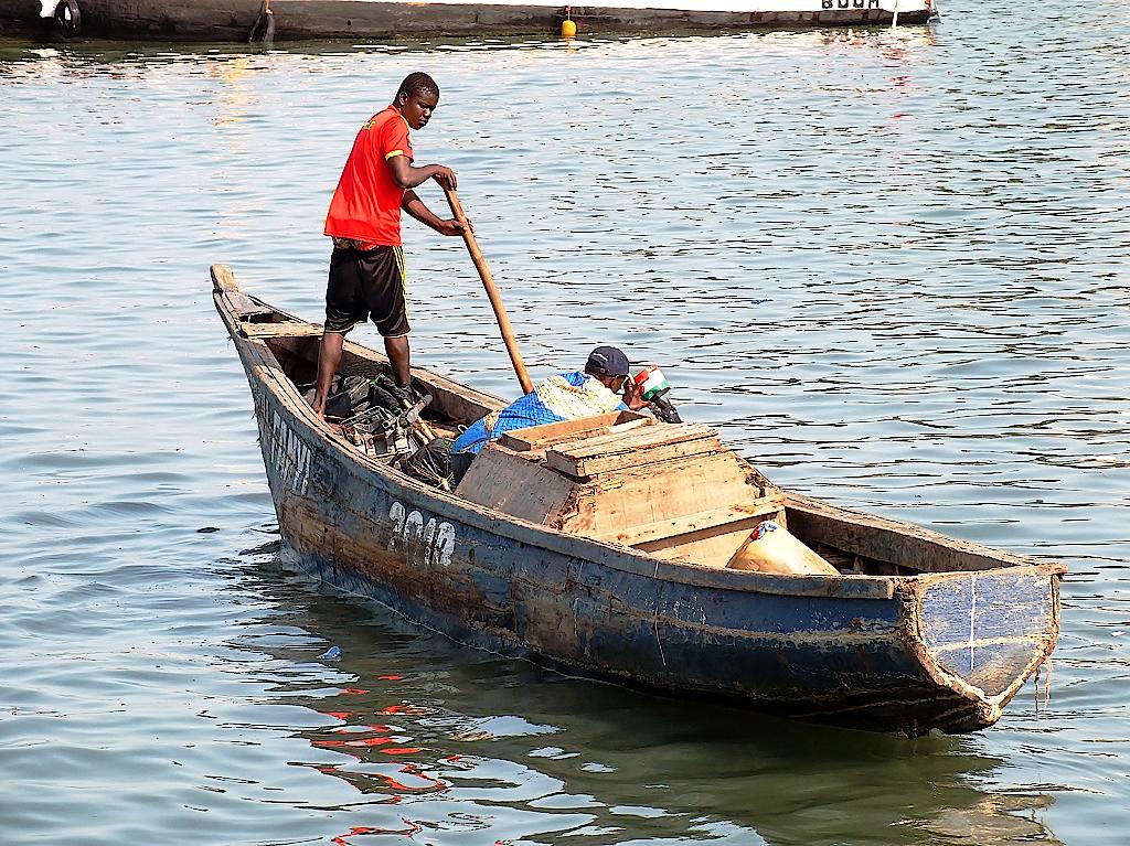 Fischer in seinem Boot; in der Mitte die Eistruhe