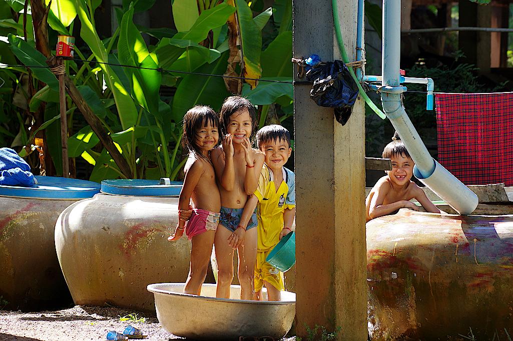 Kinder baden im Schatten der Pfahlbauten