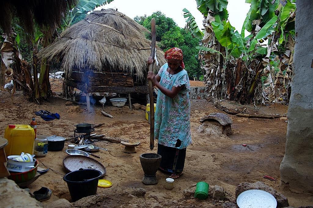 Eine Frau zerstößt in einem Holzmörser Mais, Wurzeln und kleine Fische.