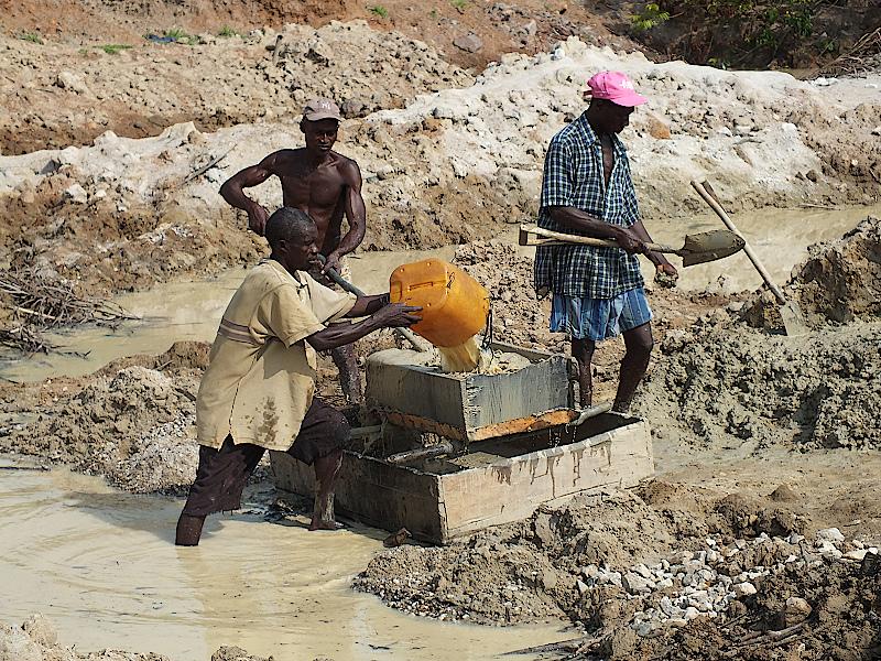 Männer stehen in den Wassertümpeln, graben und sieben