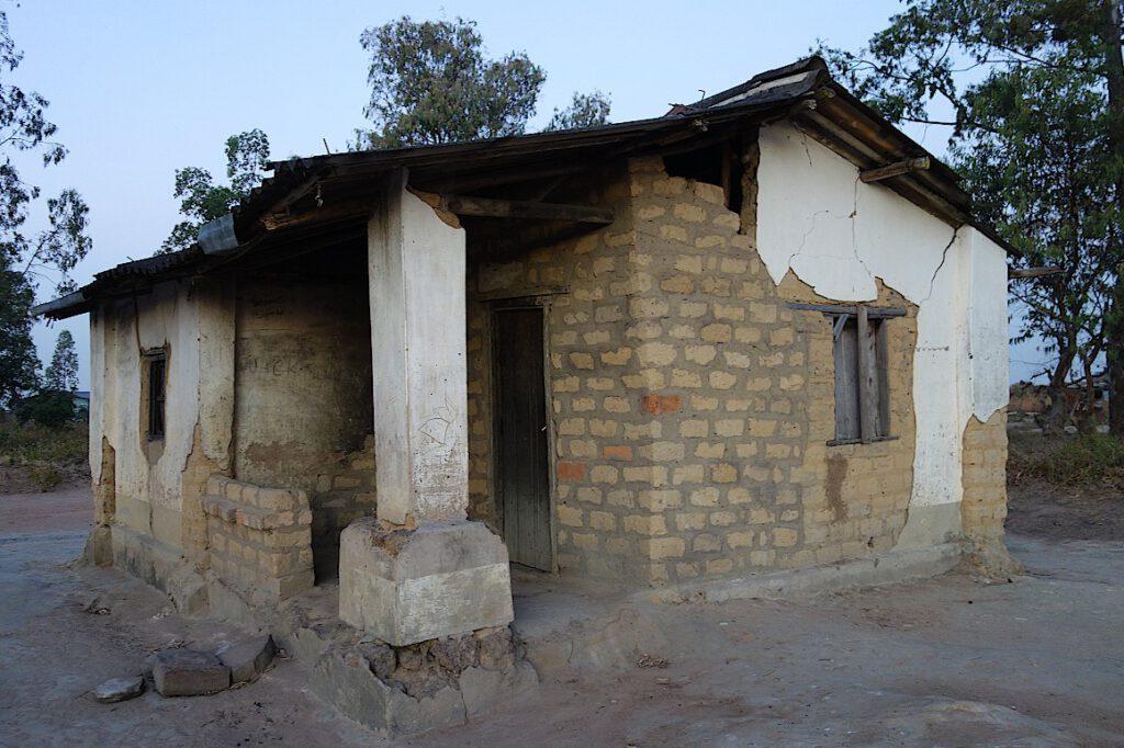Zusammengefallenes Haus, das notdürftig wieder aufgebaut wurde